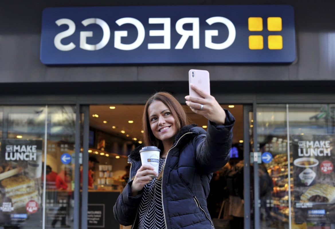 girl taking selfie with a greggs shop front